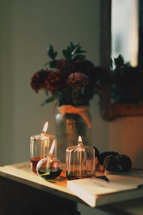 Lighted Candles on Table Near Flowers