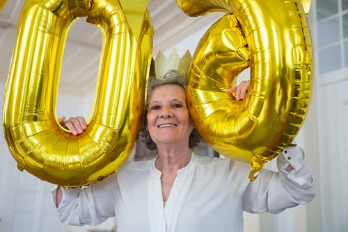 Elderly Woman Smiling while Holding Balloons
