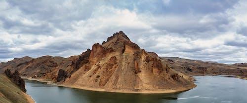 Brown Rocky Mountain Beside Body of Water