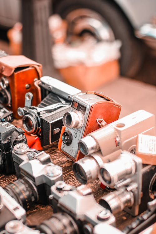 Brown and Silver Camera on Brown Wooden Table