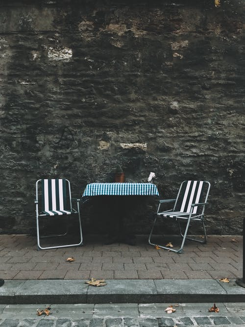 2 White and Black Folding Chairs Beside Gray Concrete Wall