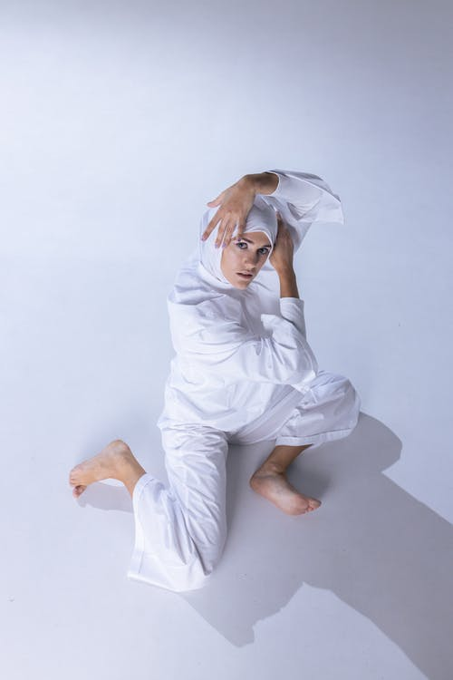 Woman in White Long Sleeve Top and Pants Sitting on White Floor
