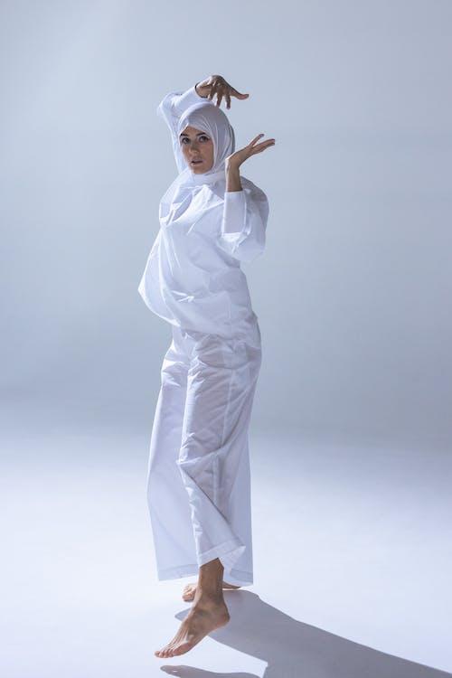 Woman in White Hijab and White Abaya Dancing