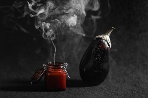 Smoke Coming Out From A Burnt Scented Candle Beside An Eggplant