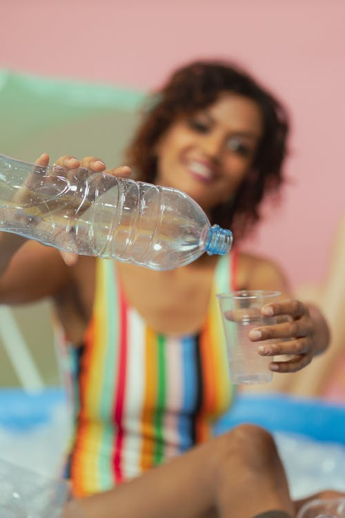 Woman in Stripes Swimsuit Pouring a Water in Plastic Cup