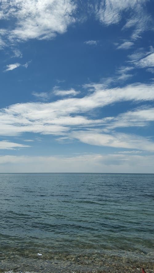 Blue Sea Under Blue Sky and White Clouds