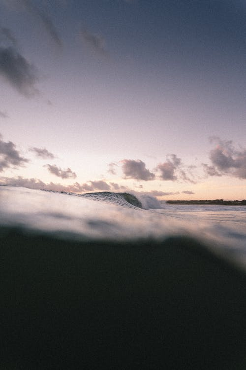 Picturesque scenery of ocean surface with waves rolling against cloudy sky in evening