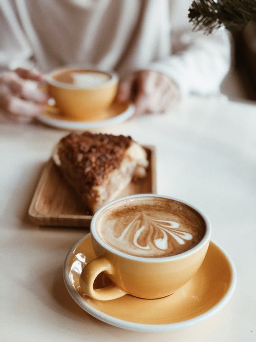 Cup of latte near piece of cake in coffee shop