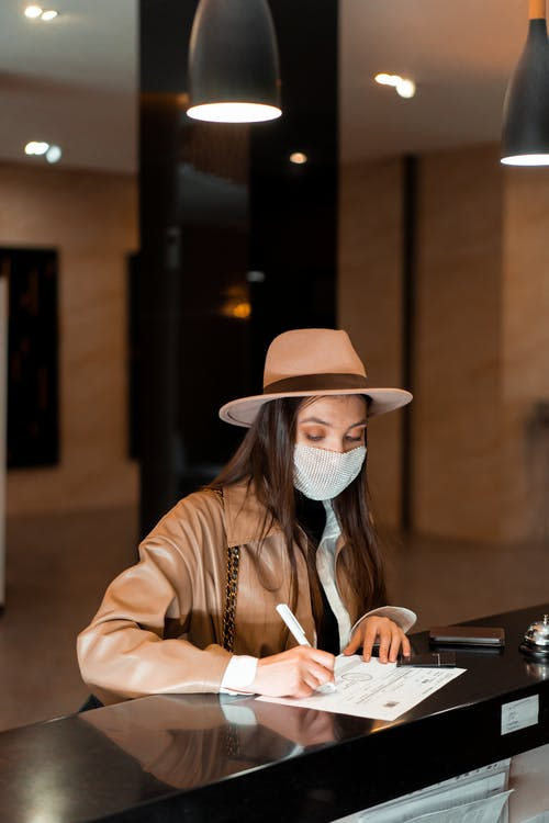 Woman in Brown Leather Jacket and White Hat