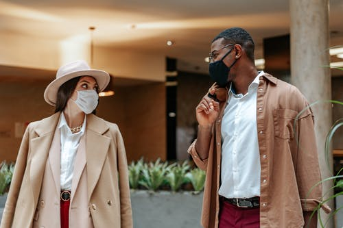 Man and Woman Having Conversation With Face Masks While Keeping Social Distancing