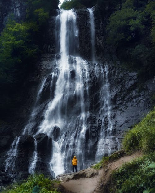 Man admiring waterfall streaming from rocky cliff