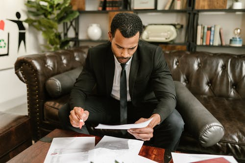 Man  Sitting on Brown Leather Sofa Looking At Documents