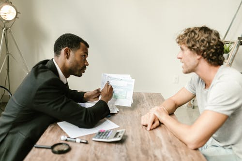 An Agent Showing Documents To His Client