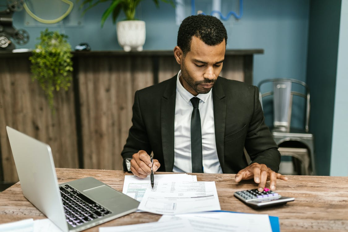 Man in Black Suit Jacket Holding Pen and Paper