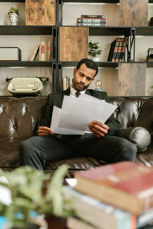 Man in Black Suit Sitting on Brown Leather Couch