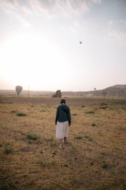 Anonymous woman walking in field
