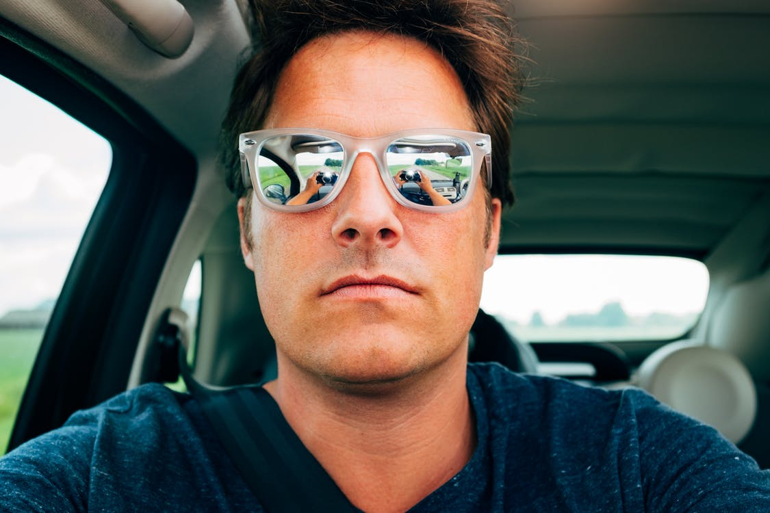 Close-up Photography of Man Wearing Sunglasses in Vehicle
