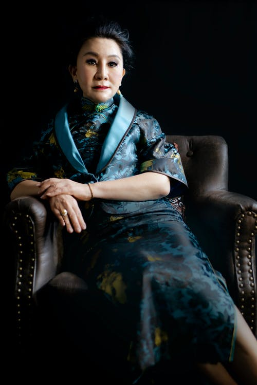Woman in Blue and White Floral Dress Sitting on Black Leather Couch