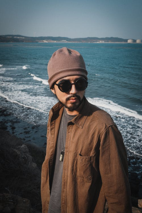 Man in Brown Leather Jacket Wearing Black Sunglasses and Gray Knit Cap Standing on Seashore during