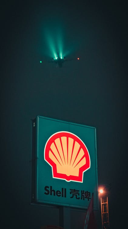 Banner with inscription and logotype of gas station located against dark sky with flying airplane at night time in city