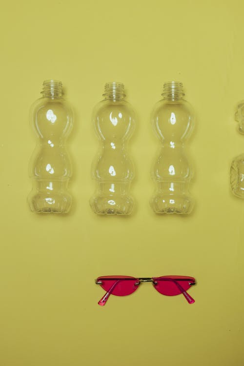 Clear Plastic Bottles on Yellow Surface