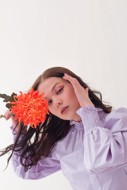 Dreamy woman with flower in studio