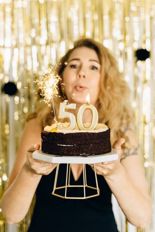 Woman Holding Cake With Lighted Candles