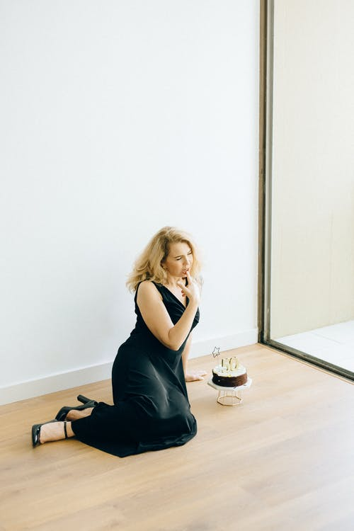 Woman in Black Tank Top and Black Pants Sitting on Floor