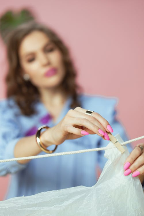 Woman Hanging the Plastic on the Clothesline