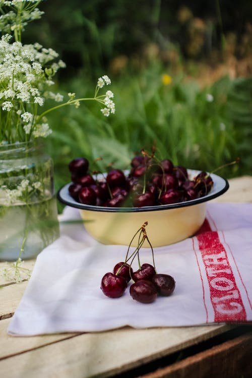 Bundles of aromatic sweet cherries in bowl on towel against jar with blossoming flowers in summer