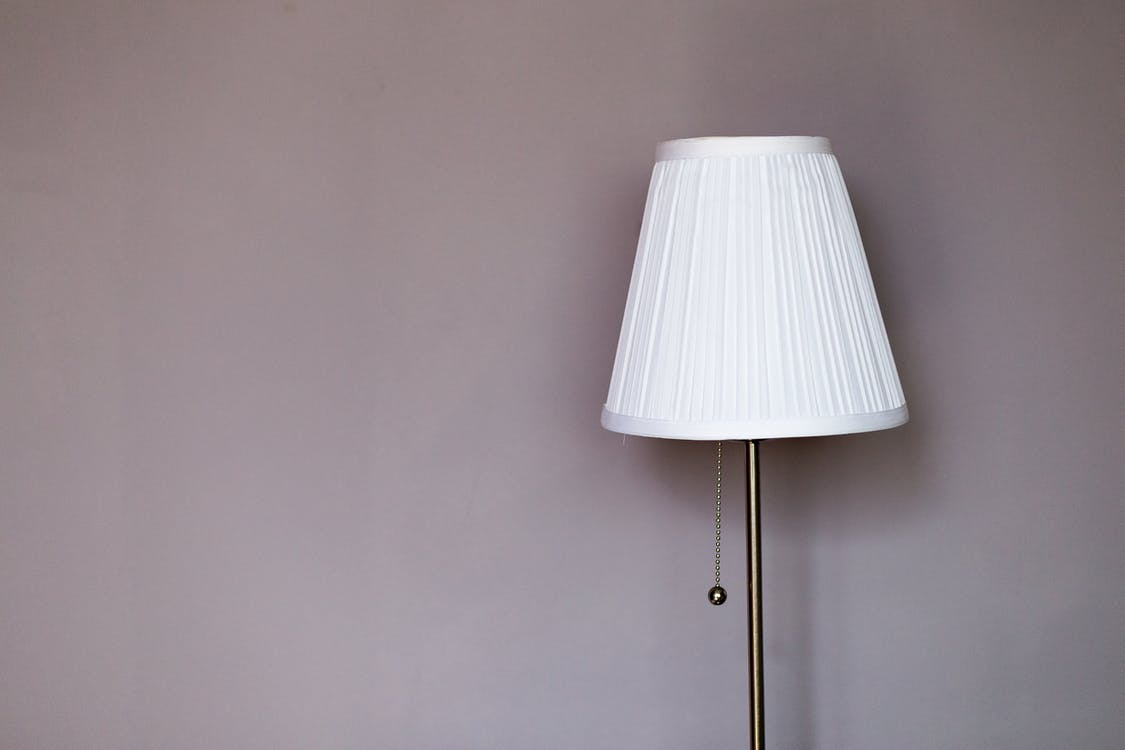 White and Grey Metal Pedestal Lamp Nearby Grey Painted Wall