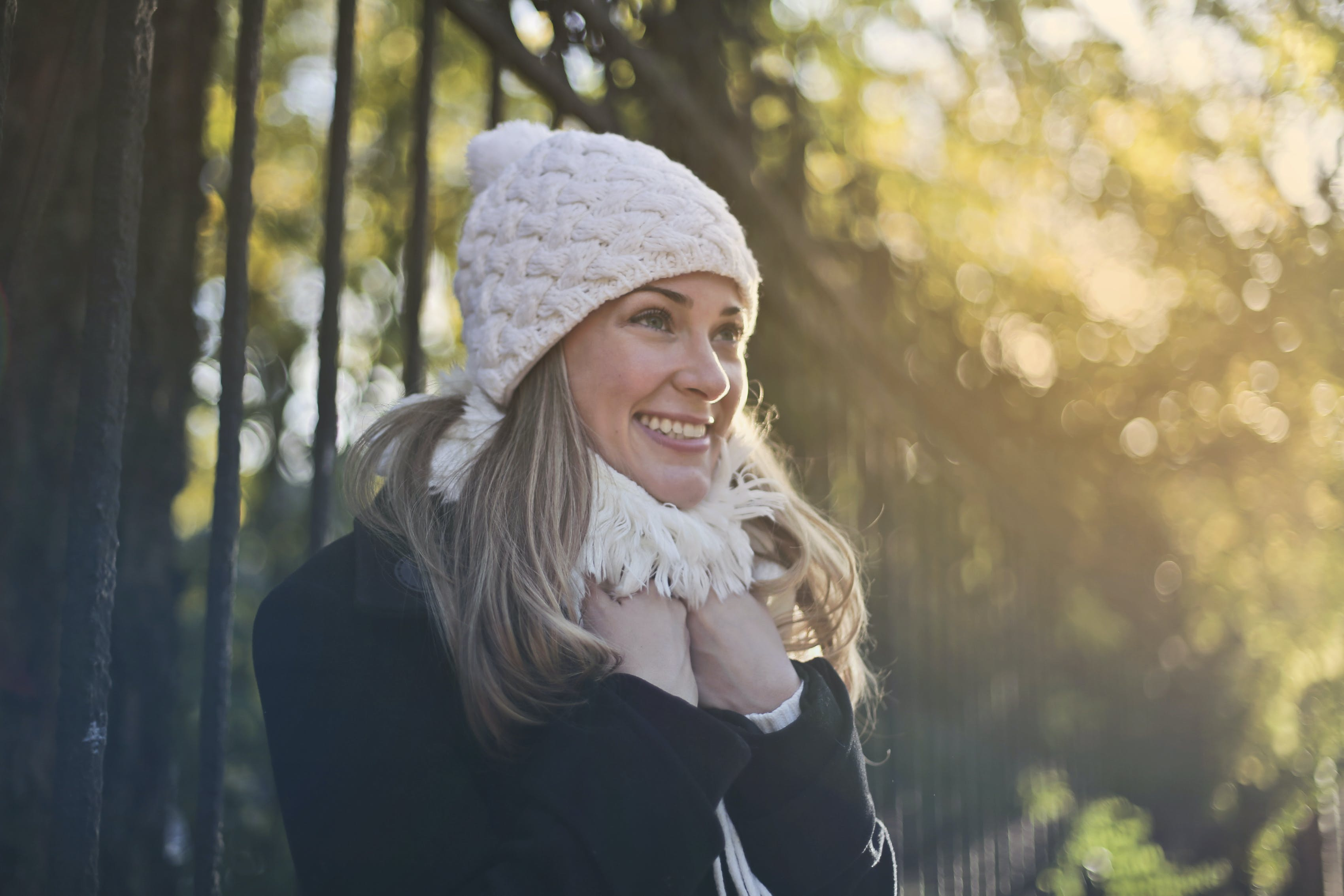 Photography of Woman in Black Jacket and White Knit Cap Smiling Next to Black Metal Fence