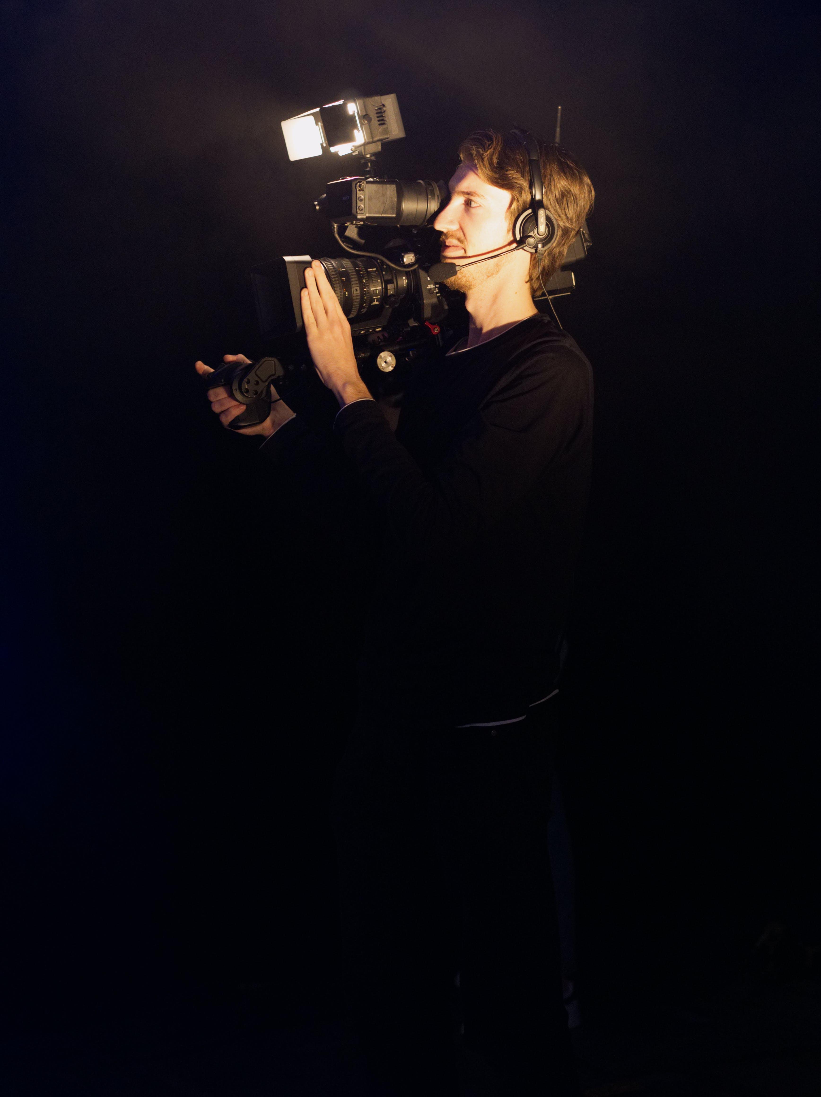 Man Wearing Black Long-sleeved Shirt Using Video Camera