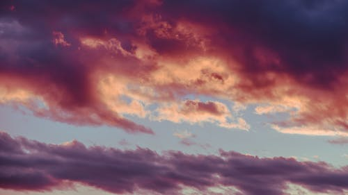 From below of picturesque sunrise with bright multicolored clouds floating in blue sky
