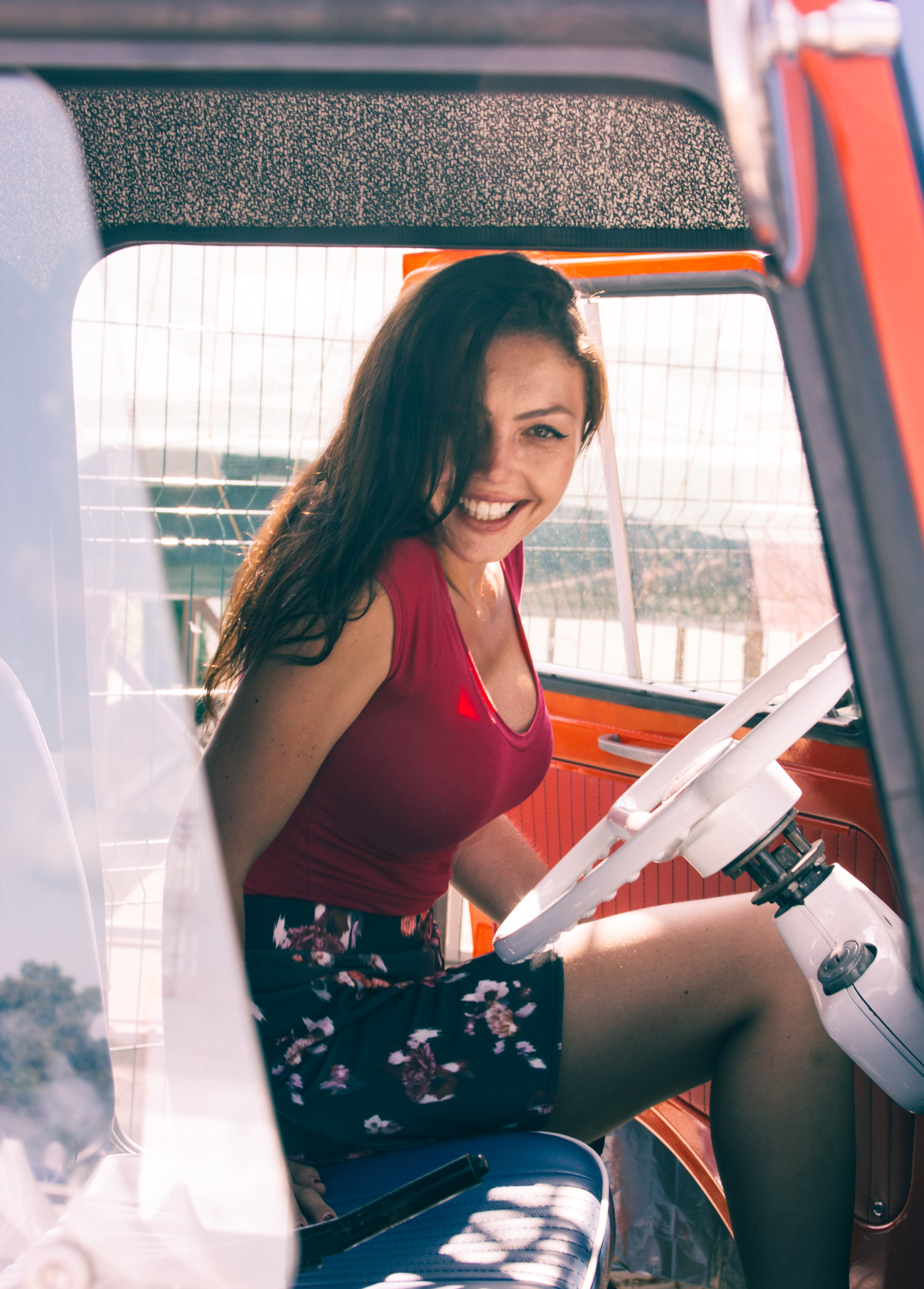 Woman in Red Shirt Sitting on Vehicle Seat at Daytime