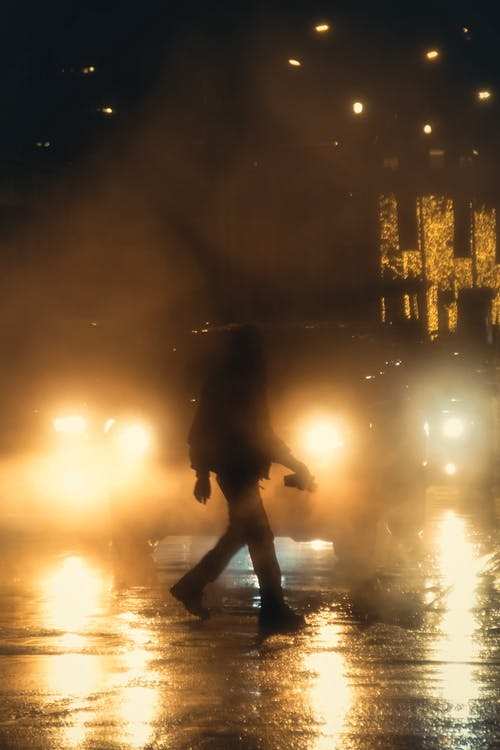 Side view of unrecognizable person walking on wet asphalt road against lights of cars in night time