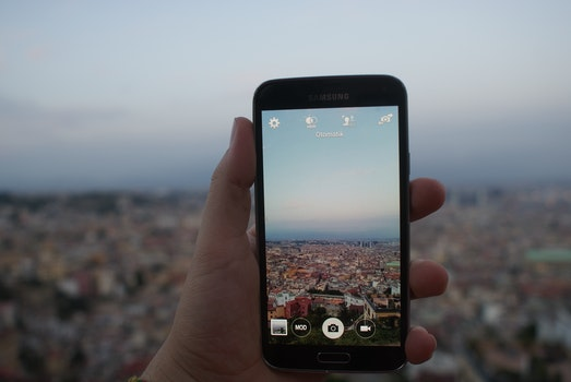 Person Holding a Black Samsung Galaxy Android Smartphone Taking a Picture of Cityscape over Blue and White Sky during Daytime