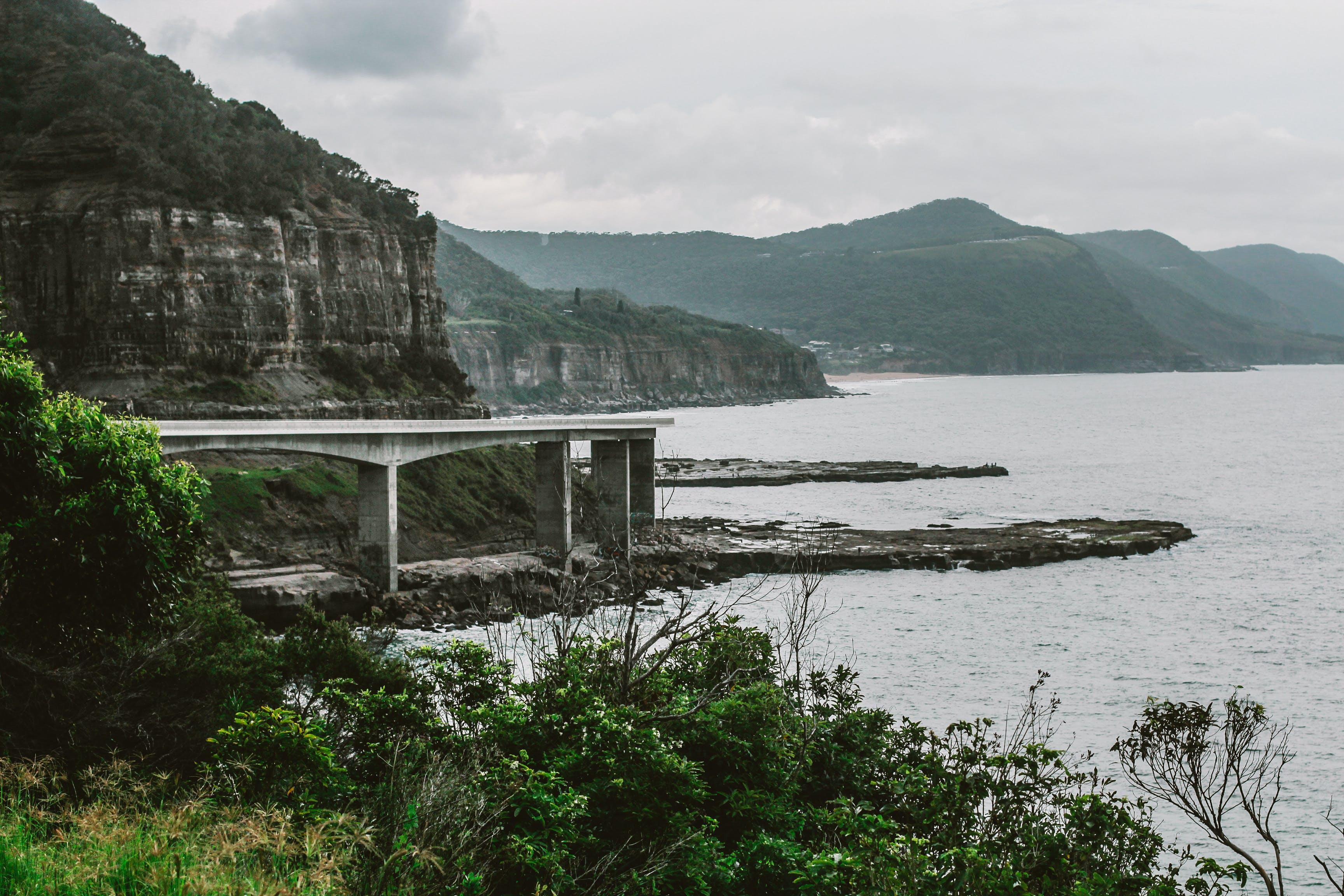 Concrete Bridge Near Mountain Above Shoreline Under Cloudy Sky