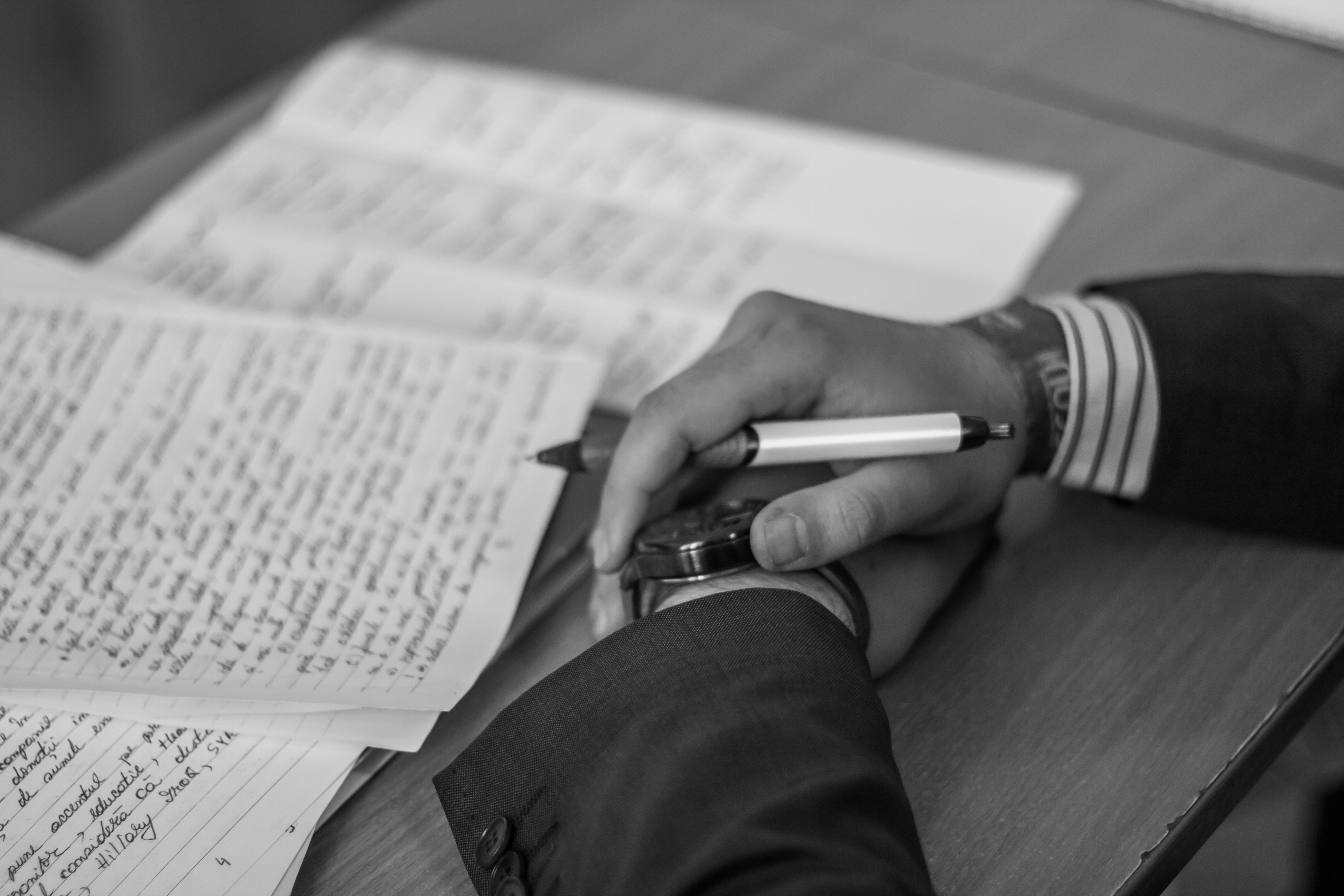 grayscale photography of person holding pen · free stock photo