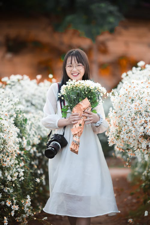 Woman in White Long Sleeve Dress Holding Bouquet of Flowers