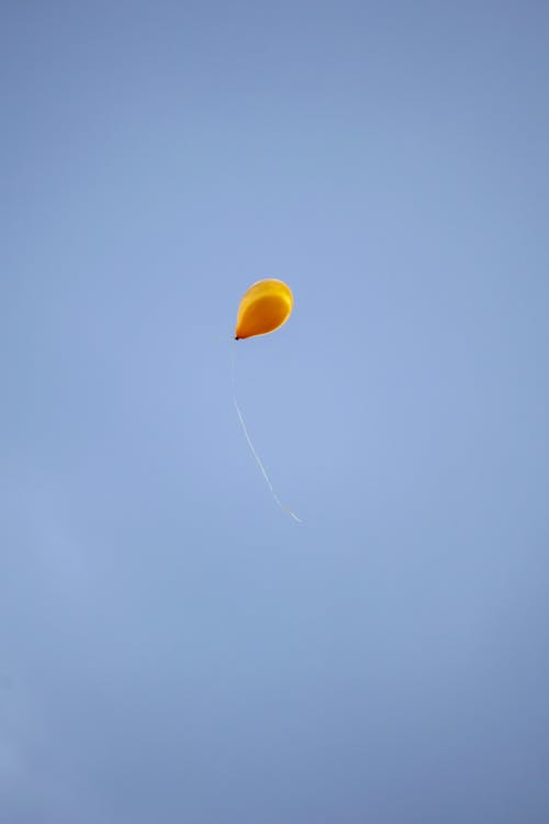 A Yellow Balloon Flying on a Blue Sky