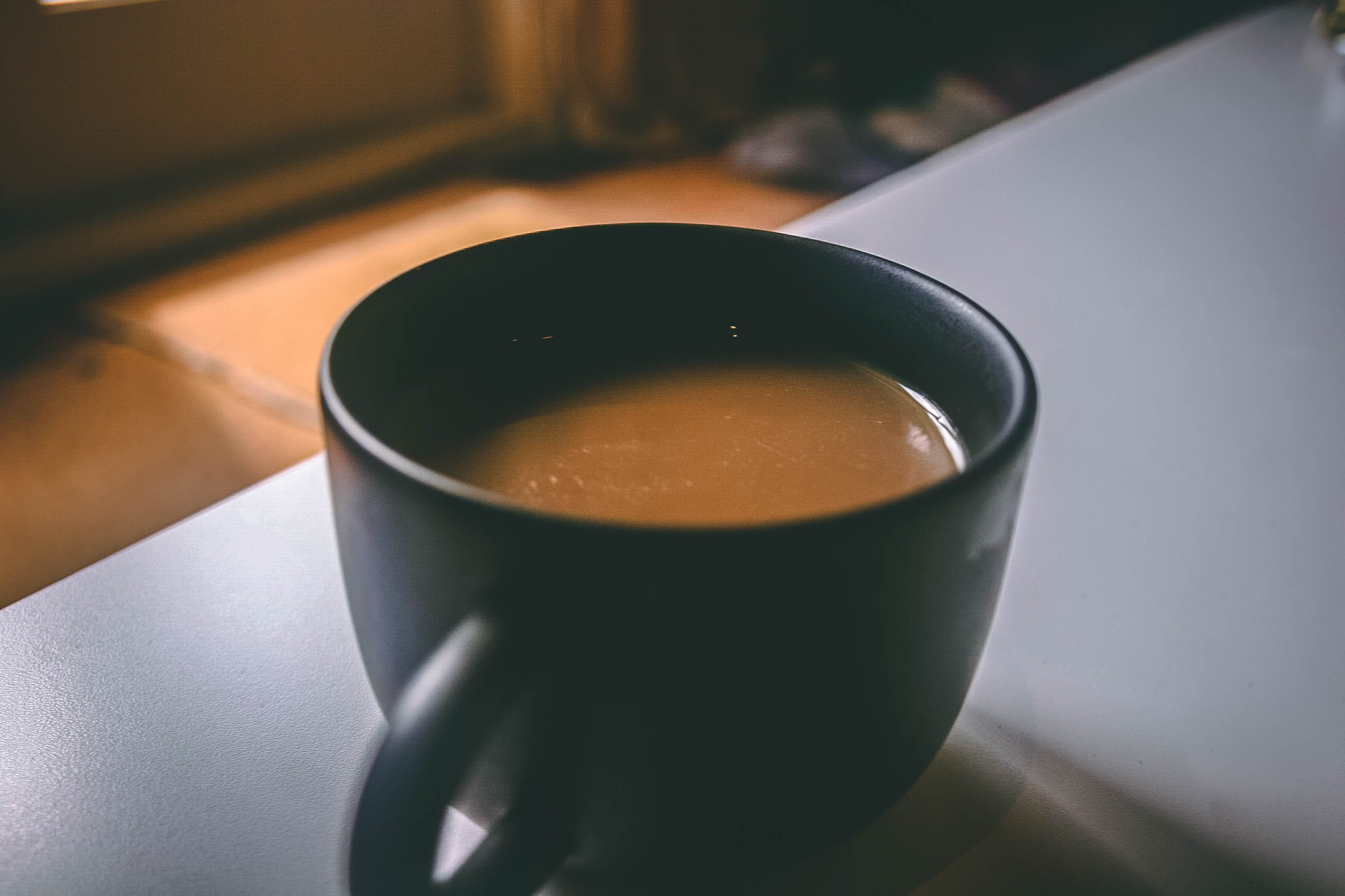Shallow Focus Photography of Black Ceramic Mug Filled With Brown Coffee on the Table