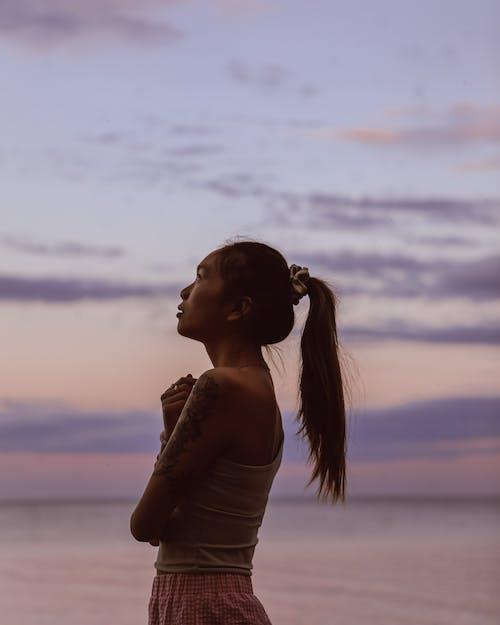 Asian woman standing on seashore at sunset
