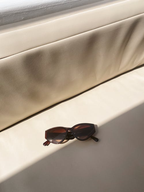 Brown Sunglasses on White Textile
