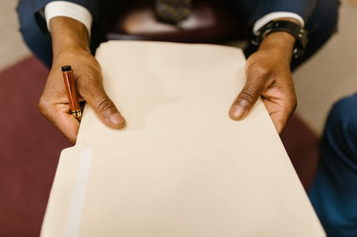 Person Wearing Gold Ring Holding White Paper