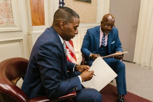 Two Men in Blue Suit Holding a Folder