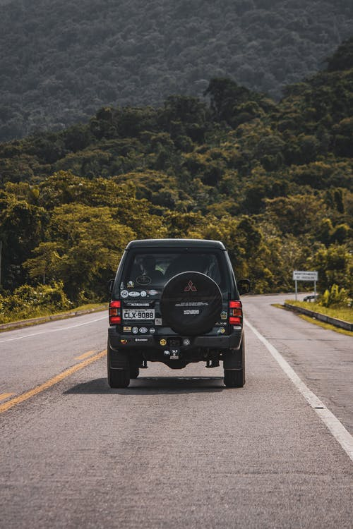 Car driving on asphalt road towards green forested hill