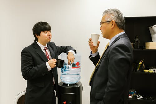 Man in Black Suit Holding White Plastic Cup