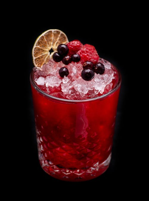 A Glass Raspberry Cocktail with Berries Topping