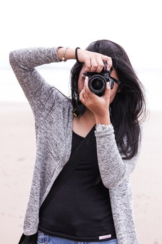Woman in Gray Cardigan and Black Shirt Holding Black Dslr Camera